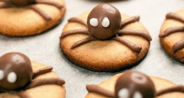 Funny delicious ginger biscuits for Halloween on the table. Set of chocolate Halloween spider cookies on paper for bake and wooden background