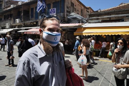 Un homme porte un masque protecteur avec le drapeau national israélien imprimé