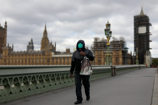 A person wearing a face mask walks past Westminster Abbey.