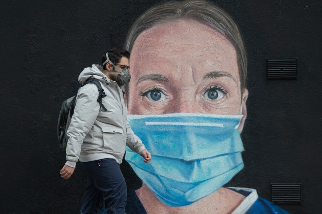 man in a face mask walks in front of a mural of a nurse with a PPE face mask on.