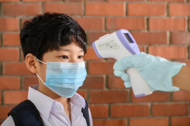 A student wearing a face mask getting his temperature taken.