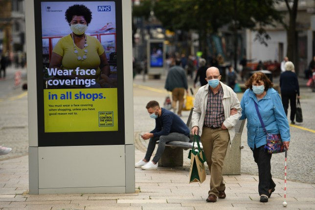 Shoppers wearing face masks walk past a sign calling for the wearing of face coverings in shops