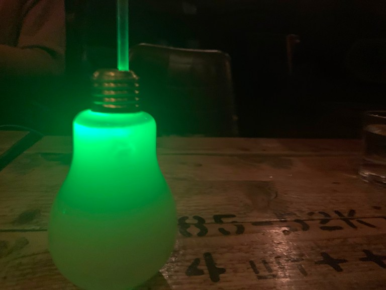 A glowing lightbulb in green, filled with liquid and with a straw sticking up at the top.