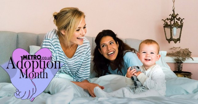 Two women playing with their baby in bed.