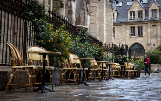 A pedestrian wearing protective a face mask walks past a deserted bistrot terrace at lunch time, in the latin quarter in central Paris, France, 25 September 2020.