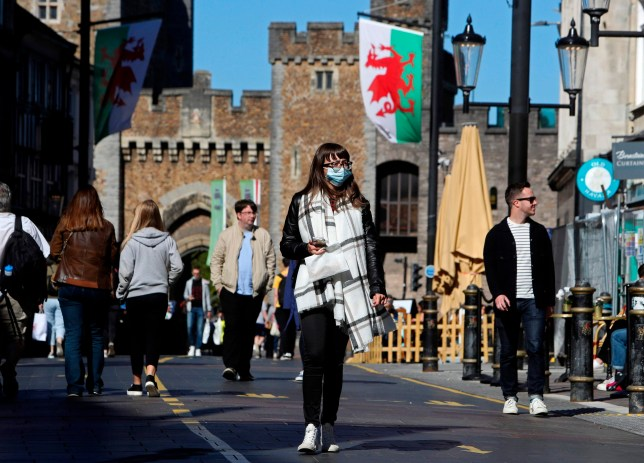 A woman in a face mask walks through Cardiff