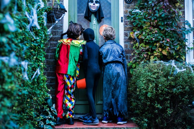 Three little boys go Trick or Treating.