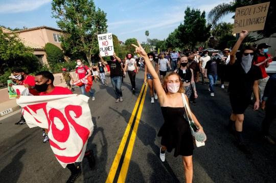 Protestors march to Amazon CEO Jeff Bezos' mansion to demand higher wages and free healthcare.