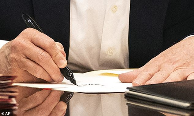 A zoom on the Trump photo signing a blank piece of paper