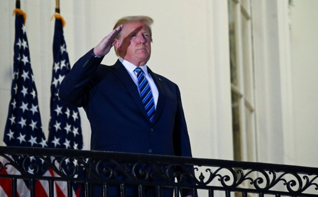U.S. President Donald Trump salutes as he poses without a face mask on the Truman Balcony of the White House after returning from being hospitalized at Walter Reed Medical Center for coronavirus disease (COVID-19) treatment, in Washington, U.S. October 5, 2020. REUTERS/Erin Scott