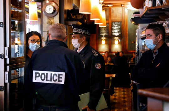 Police officers check a restaurant in Paris on October 6, 2020, during a patrol to inspect the implementation of new sanitary measures aimed at curbing the spread of the Covid-19 (novel coronavirus) outbreak in the French capital. - Bars and cafes in Paris and its nearest suburbs, placed on maximum coronavirus alert from October 5, will be shuttered for two weeks from October 6 under new measures to slow the rapid spread of Covid-19 cases. Restaurants will remain open provided they respect new safety measures including providing sanitising hand gel, limiting patrons to six a table with at least a meter between seats, and allowing diners to remove their masks only for eating. (Photo by THOMAS COEX / AFP) (Photo by THOMAS COEX/AFP via Getty Images)