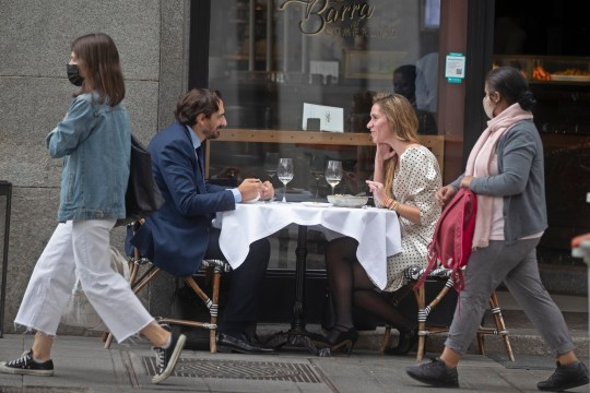 A couple have lunch outside a bar in Madrid, Spain, Thursday, Oct. 8, 2020. A court in Madrid has struck down a national government order that imposed a partial lockdown due to the coronavirus pandemic in the Spanish capital and its surrounding suburbs, siding with regional officials who had resisted stricter measures against one of Europe's most worrying virus clusters. (AP Photo/Paul White)