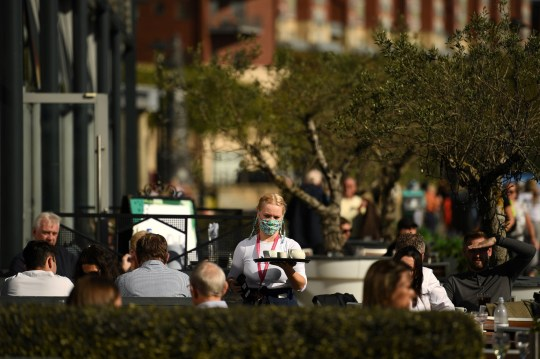 A waiter wearing a face mask or blanket due to the COVID-19 pandemic, transports drinks to customers to outdoor tables at a restaurant in Newcastle, north-east England, on September 29, 2020, after stricter restrictions have been put in place to help mitigate the spread. of COVID-19.