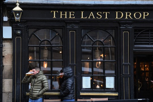 EDINBURGH - OCTOBER 09: Members of the public enjoy a drink at the Last Drop pub in the Grassmarket prior to last orders at 6pm on October 9, 2020 in Edinburgh, Scotland. Pubs and restaurants in the central belt of Scotland close their doors for a fortnight while from 6pm in tough new coronavirus measures set out by the Scottish Government. (Photo by Jeff J Mitchell/Getty Images)