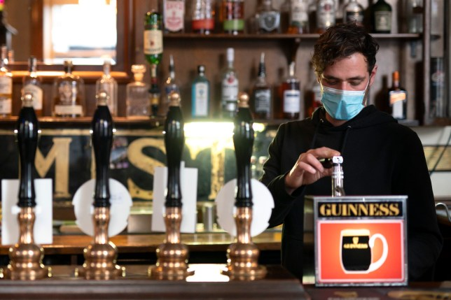 A member of staff pours a drink, at the Dispensary pub in Liverpool, England, Monday Oct 12, 2020.