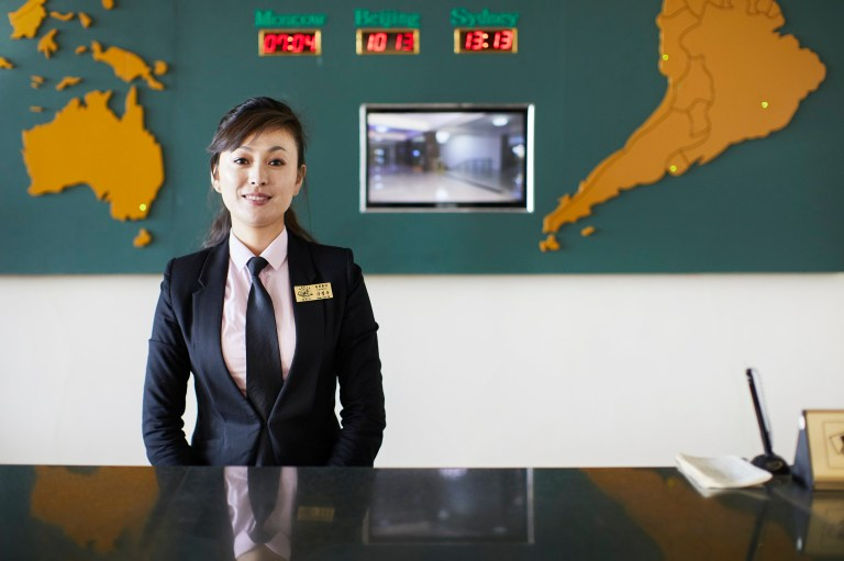 hotels of pyongyang book captures hotel interiors and staff in north korea's capital city: hotel staff at reception desk
