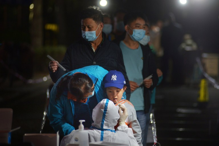 A medical worker in protective suit collects a swab from a child for nucleic acid testing, following new cases of coronavirus disease (COVID-19) in Qingdao, Shandong province, China October 13, 2020. Picture taken October 13, 2020. cnsphoto via REUTERS ATTENTION EDITORS - THIS IMAGE WAS PROVIDED BY A THIRD PARTY. CHINA OUT.