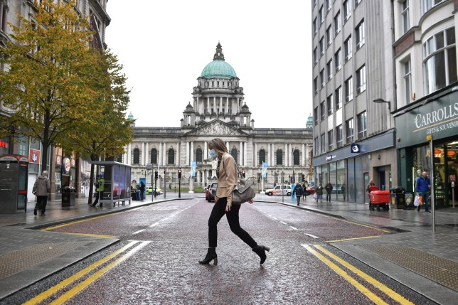 A shopper wearing a face mask walks past Belfast City Hall.