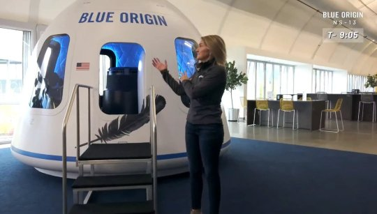 A woman showing off the Blue Origin space capsule that Jeff Bezos will use to fly to orbit