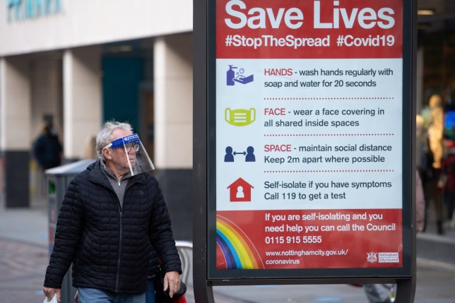 A man wearing a face shield walks past a coronavirus advice sign.