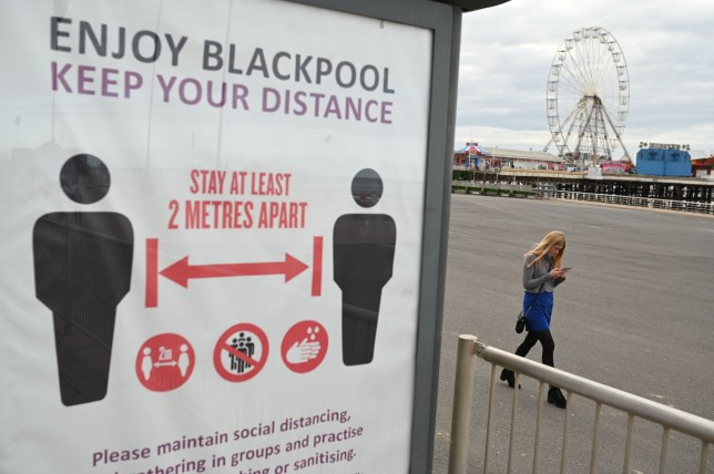A woman walks along the seafront past a sign encouraging social distancing as a precaution against the transmission of the novel coronavirus in Blackpool, Lancashire on October 16, 2020, as the number of cases of Covid-19 rises. - Another 1.5 million people in England will be placed under the toughest coronavirus restrictions this weekend as Lancashire moves into Tier 3. (Photo by Oli SCARFF / AFP) (Photo by OLI SCARFF/AFP via Getty Images)