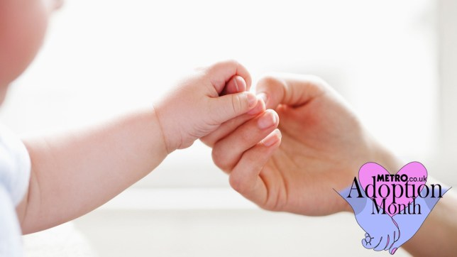 A close up shot of a baby holding a gorwn up's hand. Adoption Month logo is also on the image