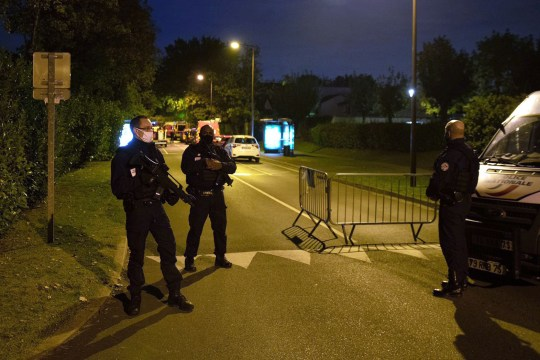 TOPSHOT - French police officers stand guard a street in Eragny on October 16, 2020, where an attacker was shot dead by policemen after he decapitated a man earlier on the same day in Conflans-Sainte-Honorine. - French anti-terror prosecutors said Friday they were investigating an assault in which a man was decapitated on the outskirts of Paris and the attacker shot by police. The attack happened at around 5 pm (1500 GMT) near a school in Conflans Saint-Honorine, a western suburb of the French capital. The man who was decapitated was a history teacher who had recently shown caricatures of the Prophet Mohammed in class. French prosecutors are treating the attack as a terror incident, which coincides with the trial of alleged accomplices of the 2015 Charlie Hebdo attackers and comes weeks after a man injured two people he thought worked for the magazine. (Photo by ABDULMONAM EASSA / AFP) (Photo by ABDULMONAM EASSA/AFP via Getty Images)