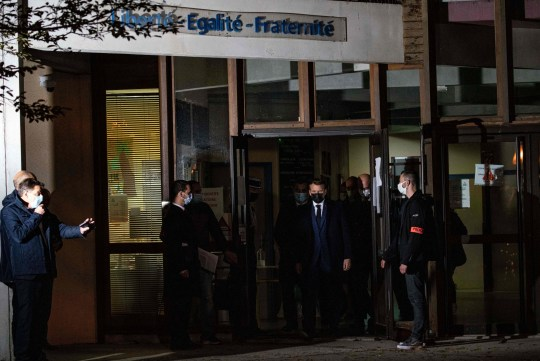 TOPSHOT - French President Emmanuel Macron (C) leaves a middle school in Conflans Saint-Honorine, 30kms northwest of Paris, on October 16, 2020, after a teacher was decapitated by an attacker who has been shot dead by policemen. - French anti-terror prosecutors said on October 16 they were investigating an assault in which a man was decapitated on the outskirts of Paris and the attacker shot by police. The attack happened at around 5 pm (1500 GMT) near a school in Conflans Saint-Honorine, a western suburb of the French capital. The man who was decapitated was a history teacher who had recently shown caricatures of the Prophet Mohammed in class. French prosecutors are treating the attack as a terror incident, which coincides with the trial of alleged accomplices of the 2015 Charlie Hebdo attackers and comes weeks after a man injured two people he thought worked for the magazine. (Photo by ABDULMONAM EASSA / POOL / AFP) (Photo by ABDULMONAM EASSA/POOL/AFP via Getty Images)