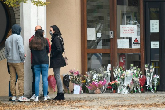 Adults and children talk next to flowers displayed at the entrance of a middle school in Conflans Saint-Honorine, 30kms northwest of Paris, on October 17, 2020, after a teacher was decapitated by an attacker who has been shot dead by policemen. - The man suspected of beheading on October 16 ,2020 a French teacher who had shown his students cartoons of the prophet Mohammed was an 18-year-old born in Moscow and originating from Russia's southern region of Chechnya, a judicial source said on October 17. Five more people have been detained over the murder on October 16 ,2020 outside Paris, including the parents of a child at the school where the teacher was working, bringing to nine the total number currently under arrest, said the source, who asked not to be named. The attack happened at around 5 pm (1500 GMT) near a school in Conflans Saint-Honorine, a western suburb of the French capital. The man who was decapitated was a history teacher who had recently shown caricatures of the Prophet Mohammed in class. (Photo by Bertrand GUAY / AFP) (Photo by BERTRAND GUAY/AFP via Getty Images)
