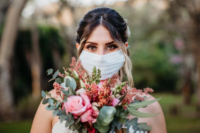 Bride Smiling behind the mask with bouquet of flowers in hand