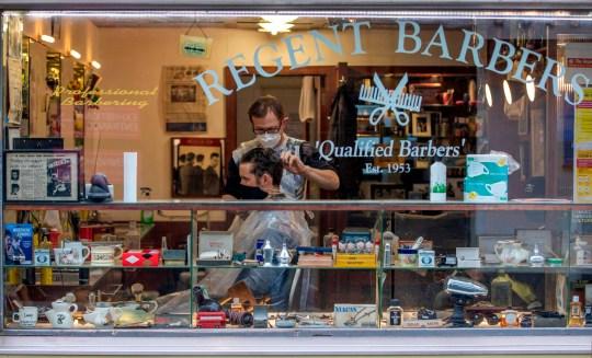 Un coiffeur portant l'EPI d'un masque facial ou d'une couverture en raison du COVID-19, coupe les cheveux d'un client dans un salon de coiffure à Dublin le 19 octobre 2020, alors que des informations selon lesquelles de nouvelles restrictions de verrouillage pourraient être imposées pour aider à atténuer la propagation du nouveau coronavirus.