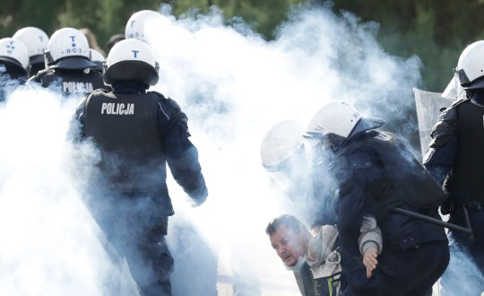 Polish police in riot gear detain protesters angry over new restrictions aimed at fighting the coronavirus pandemic, in Warsaw, Poland, Saturday, Oct. 24, 2020.