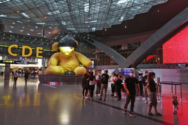 Travellers wearing masks walk past a giant 23-foot-long canary-yellow sculpture of a teddy bear sitting inside a lamp, at Hamad International Airport in the Qatari capital Doha, almost empty due to the COVID-19 coronavirus pandemic, on April 1, 2020. (Photo by KARIM JAAFAR / AFP) (Photo by KARIM JAAFAR/AFP via Getty Images) - 8882537