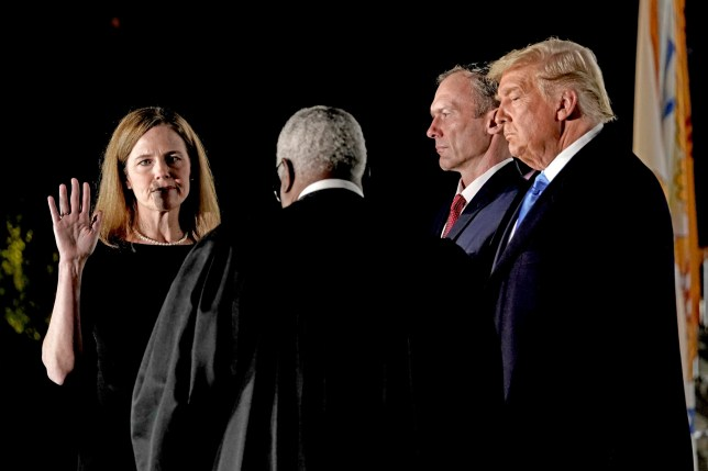 epa08776686 Associate Justice of the Supreme Court Clarence Thomas (C) administers the oath of office to Judge Amy Coney Barrett (L) to be Associate Justice of the Supreme Court, as US President Donald J. Trump and her husband Jesse M. Barrett look on, on the South Lawn of the White House in Washington, DC, USA, 26 October 2020. EPA/Ken Cedeno / POOL