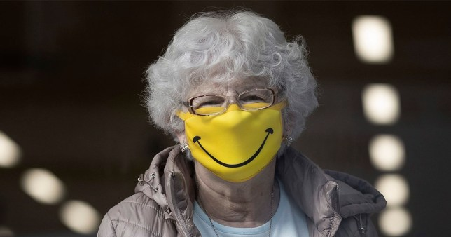 A woman smiles while wearing a novelty face mask in a shop on October 1, 2020 in Barry, Wales.