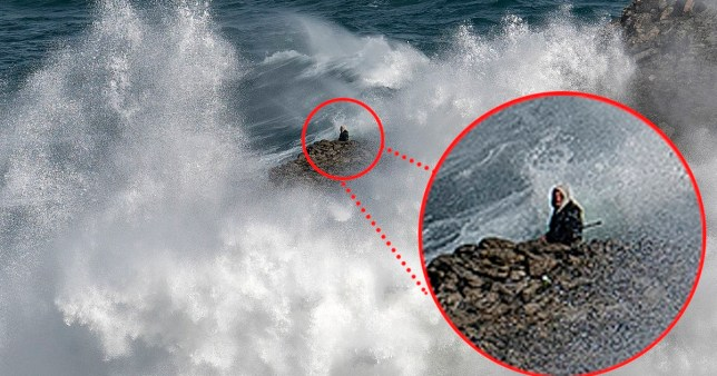 A fisherman braves huge waves on cliffs in Cornwall