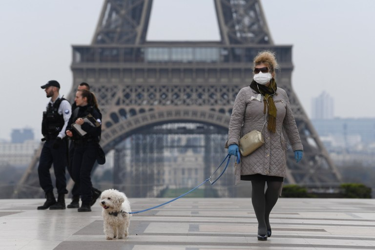 PARIS, FRANCE - MARCH 18: A woman wearing a protective mask walks her dog on the Esplanade du Trocadero square in front of the Eiffel Tower the second day after the announcement by French President Emmanuel Macron of the confinement of the French due to an outbreak of coronavirus pandemic (COVID-19) on March 18, 2020 in Paris, France. From Tuesday, March 17 at noon for at least two weeks, the French will have to stay at home, under penalty of sanctions, unless travel is absolutely necessary, announced the head of state. President launched the war against the coronavirus and placed France in containment without ever saying the word. The Coronavirus epidemic has exceeded 7,900 dead for more than 198,000 infections across the world. (Photo by Pascal Le Segretain/Getty Images )