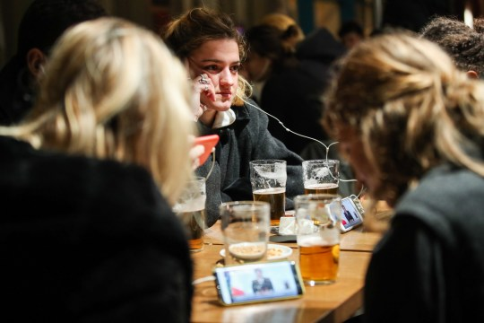 Customers in a cafe watch the televised statement of French President Emmanuel Macron
