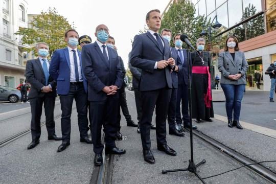 Le président français Emmanuel Macron (C) s'adresse à la presse devant la basilique Notre-Dame de l'Assomption à Nice le 29 octobre 2020 après qu'un homme armé d'un couteau ait tué trois personnes à l'église, tranchant la gorge d'au moins un des eux, dans ce que les officiels considèrent comme la dernière attaque jihadiste pour secouer le pays.  (Photo par ERIC GAILLARD / POOL / AFP) (Photo par ERIC GAILLARD / POOL / AFP via Getty Images)