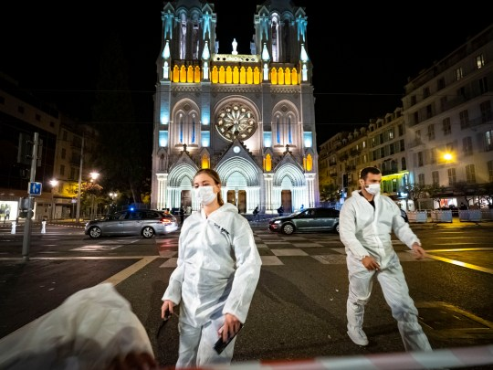 Forensic officers work at night in front of Notre Dame Basilica on October 29, 2020 in Nice, France. A man armed with a knife fatally attacked three people in the church, located in the heart of the city.