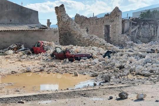 Cette photo montre une voiture détruite et des bâtiments effondrés après un tremblement de terre sur l'île de Samos