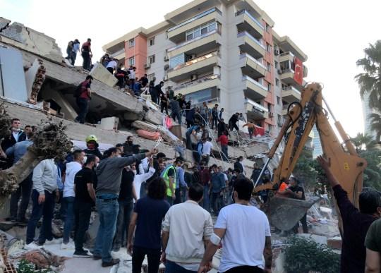 Les secouristes et la population locale tentent de sauver les résidents piégés dans les débris d'un bâtiment effondré, à Izmir en Turquie
