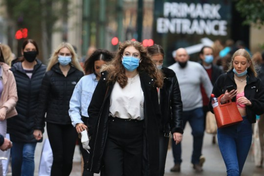 Shoppers walk wearing face masks in the centre of Leeds, West Yorkshire, northern England