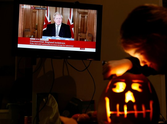 8-years-old Alice Wilkinson carves a halloween pumpkin at her home as Britain's Prime Minister Boris Johnson speaks at a news conference