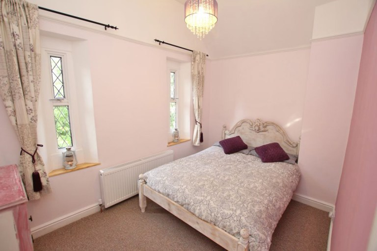 gatehouse with its own turret for sale - bedroom with pink walls and purple bedding