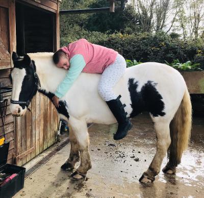 quinn, who shares her tourettes on tiktok, on a horse