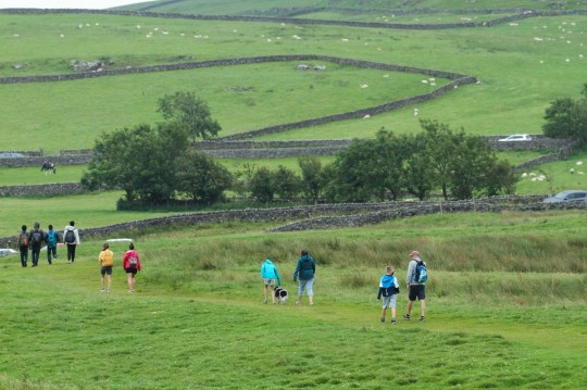 A group of hikers climb down a hill on Hope Valley.