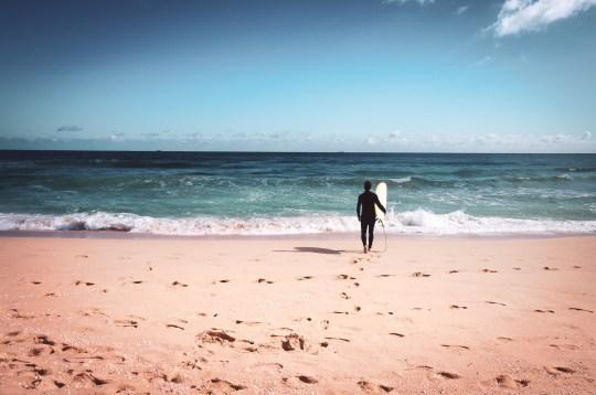 Full Length Of Man With Surfboard On Beach Against Sky