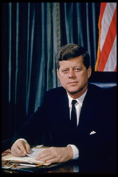 Pres. John F. Kennedy sitting at his desk, w. flag