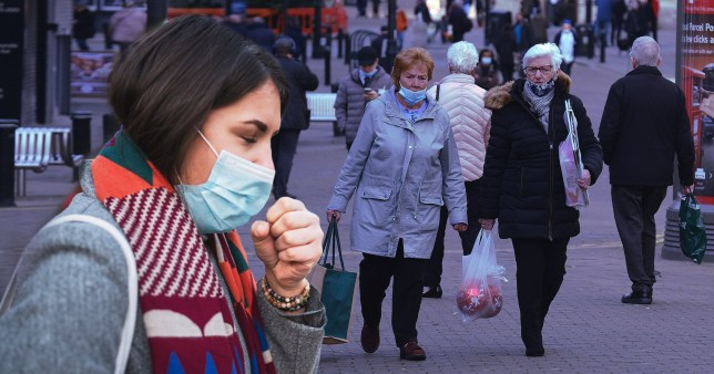 Woman wearing a face mask coughing